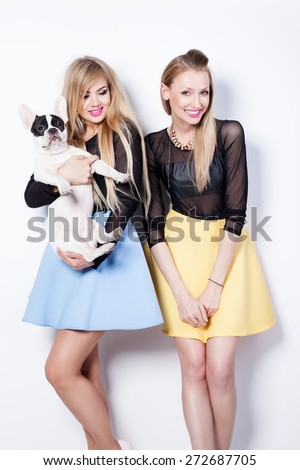 Happy young beautiful two girlfriends posing in studio with pug dog. Girls smiling. - stock photo