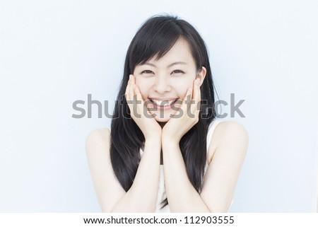 happy young beautiful woman against pale blue background