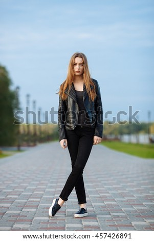 Happy young beautiful woman in black leather jacket black jeans slip-on posing for model tests in the summer park