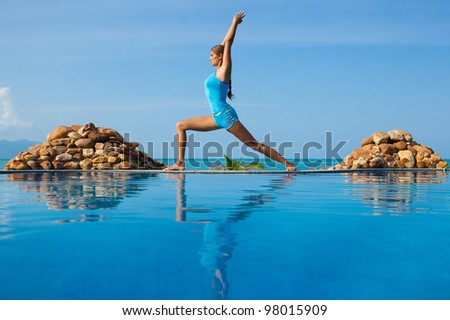 Happy young beautiful woman in yoga poses on the beach - stock photo