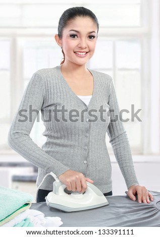 Happy young beautiful woman ironing clothes - stock photo