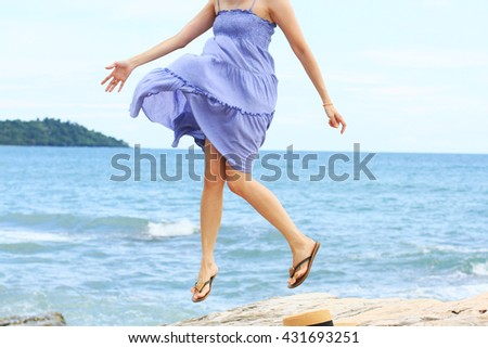 Happy young beautiful woman jumping on the beach - stock photo