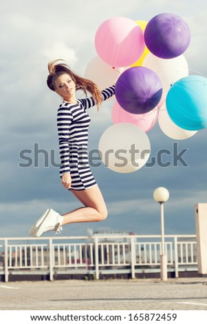 Happy young beautiful woman jumping with colorful latex balloons. Outdoors, lifestyle - stock photo