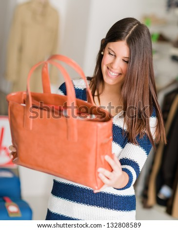 Happy Young Beautiful Woman Looking At Hand Bag, Indoors - stock photo