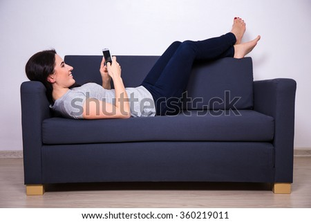 happy young beautiful woman lying on sofa and using smart phone at home