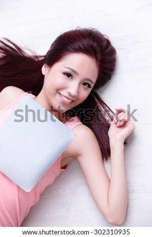 Happy young beautiful woman relax lying and using digital tablet pc, asian beauty - stock photo