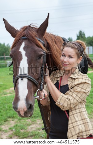 Happy young beautiful woman touching muzzle of chestnut horse
