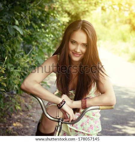 Happy young beautiful woman with retro bicycle. Portrait of fresh girl with cycle over summer outdoor, image toned. - stock photo