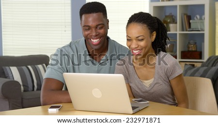 Happy young black couple laughing and watching funny video on laptop - stock photo