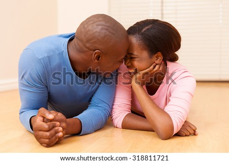 happy young black couple lying on floor in their new house - stock photo