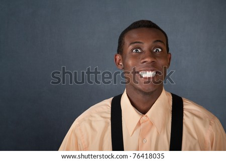 Happy young Black man on gray background with big grin - stock photo