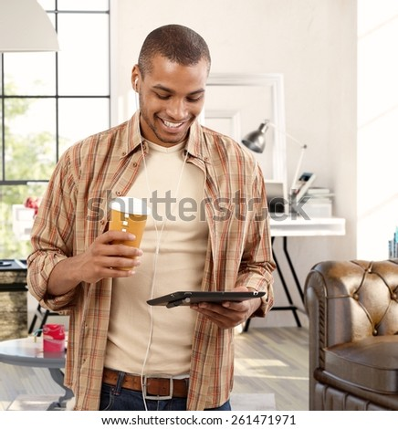 Happy young black man using tablet at home, drinking coffee. - stock photo