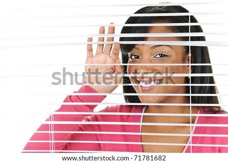 Happy young black woman looking through horizontal venetian blinds - stock photo