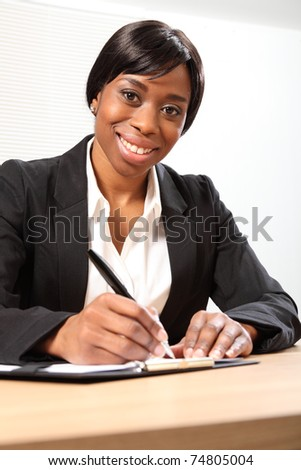 Happy young black woman working in office sitting to her desk signing a document. Picture taken from low angle. - stock photo