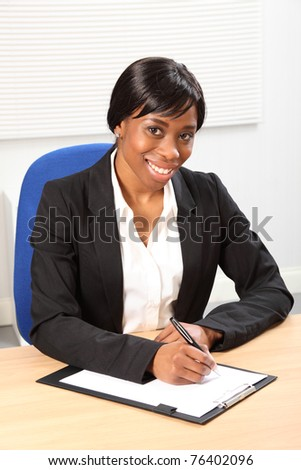 Happy young black woman working in office sitting to her desk signing a document. She is looking up from signing a paper document with a beautiful smile. Picture taken from high angle. - stock photo