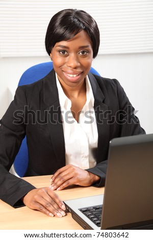 Happy young black woman working in office sitting to her desk using her laptop, with a beautiful smile. Picture taken from high angle looking downward. - stock photo