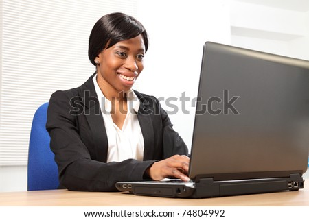 Happy young black woman working in office sitting to her desk using her laptop, with a beautiful smile. Picture taken from low angle looking upwards. - stock photo