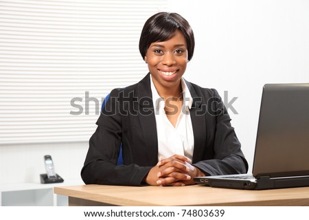 Happy young black woman working in office sitting to her desk with a beautiful smile - stock photo