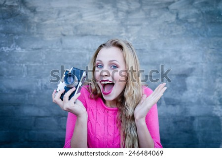 Happy young blond surprised woman with retro photo camera over brick wall copy space background - stock photo