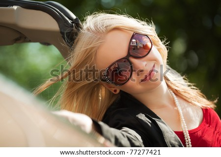 Happy young blond with a new convertible - stock photo