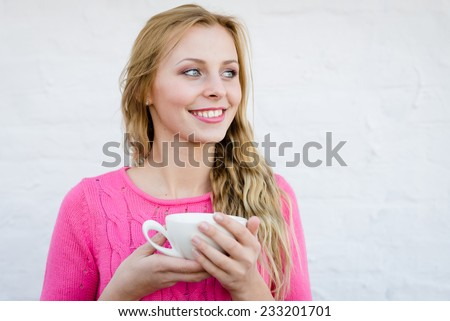 Happy young blond woman drinking hot tea or coffee and looking joyful over pin brick wall copy space background