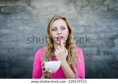 Happy young blond woman drinking hot tea or coffee and looking puzzled over gray brick wall copy space background - stock photo
