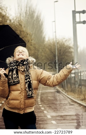 Happy young blond woman in a rainy day. - stock photo