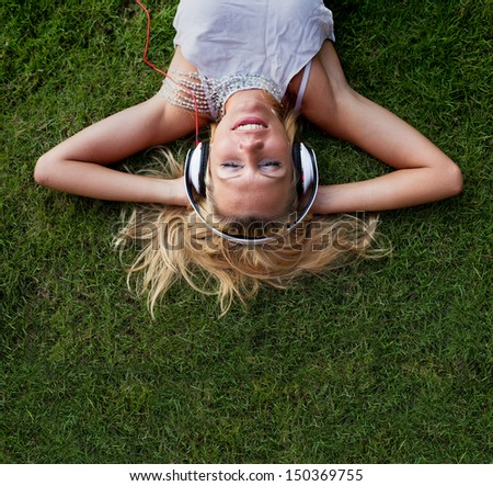 happy young blond woman in headphones on the grass - stock photo