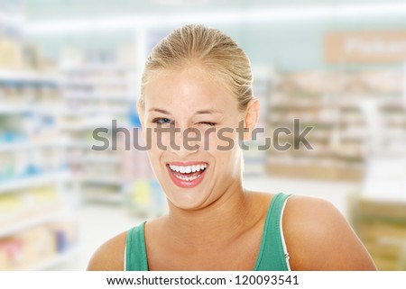 Happy young blond woman in store blinking. - stock photo