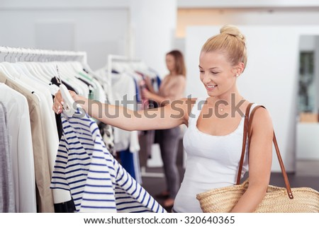 Happy young blond woman shopping for clothes holding up a striped top in a fashion boutique with a smile - stock photo