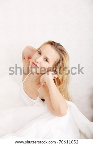 Happy young blond woman stretching in bed