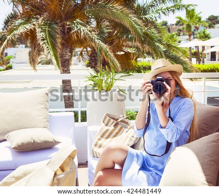 Happy young blond woman taking photo with camera on outdoor patio sofa furniture. Beautiful woman at hotel resort terrace smiling for picture enjoying modern luxury living - stock photo