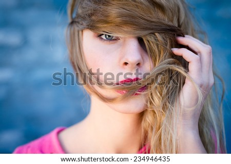 Happy young blond woman with pink lipstick wrapped her face in long hair over blue brick wall copy space background - stock photo
