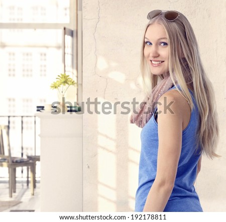 Happy young blonde casual caucasian woman at vintage home. Looking back at camera, smiling, standing, sunglasses. - stock photo