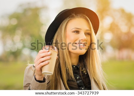 Happy young blonde Caucasian woman in park in autumn wearing trench coat and fedora hat holding a cup of takeaway coffee. Horizontal, retouched, vibrant colors. - stock photo