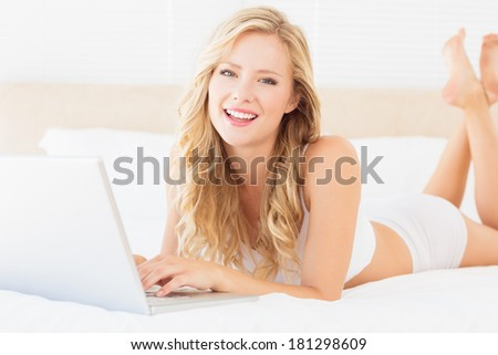 Happy young blonde lying on her bed using laptop at home in the bedroom - stock photo