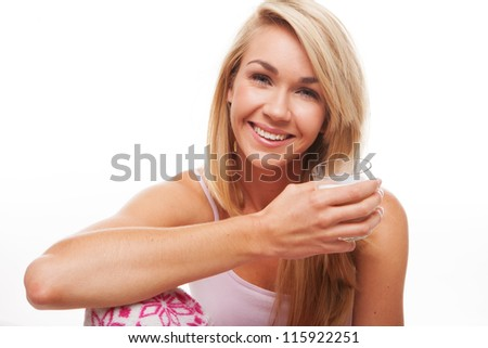 Happy young blonde woman sitting drinking a glass of fresh healthy milk isolated on white