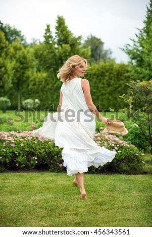 Happy young blonde woman walking barefoot on the green grass. Summer holidays lifestyle concept - stock photo