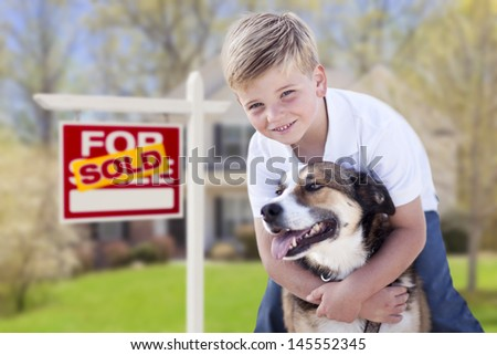 Happy Young Boy and His Dog in Front of Sold For Sale Real Estate Sign and House. - stock photo