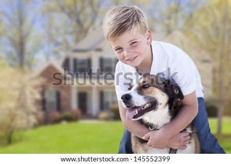 Happy Young Boy and His Dog in Front Yard of Their House. - stock photo