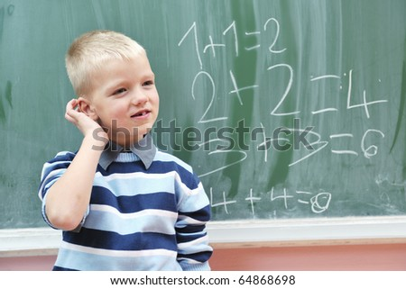 happy young boy at first grade math classes solving problems and finding solutions