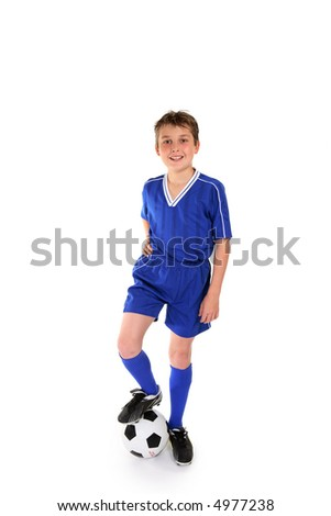 Happy young boy dressed in soccer gear rests his boot on a soccer ball - stock photo