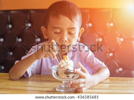 Happy young boy eating a tasty ice cream