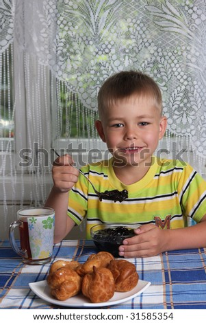 Happy young boy eating jam - stock photo