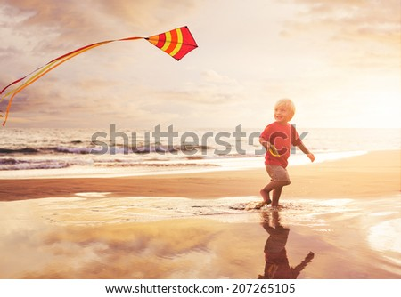 Happy young boy flying kite on the beach at sunset - stock photo