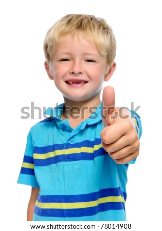 Happy young boy has his thumbs up; selective focus on hand - stock photo