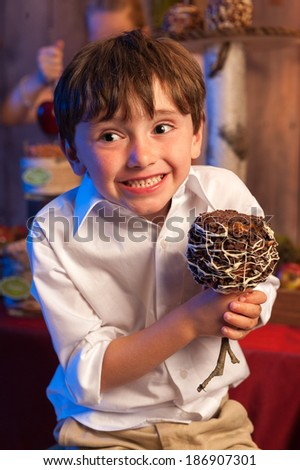 Happy young boy holding a candy apple - stock photo