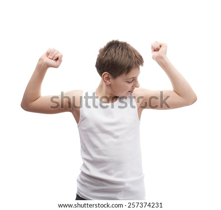 Happy young boy in a sleeveless white shirt looking at his biceps muscles, composition isolated over the white background - stock photo