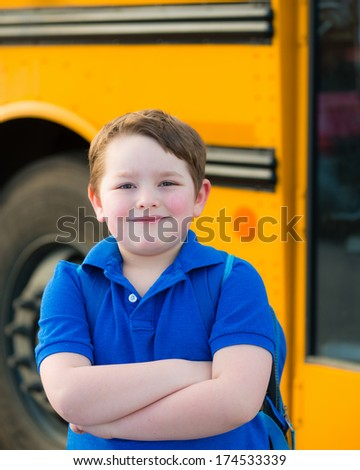 Happy young boy in front of school bus going back to school - stock photo