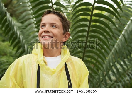 Happy young boy in raincoat standing in front of large fern during field trip - stock photo